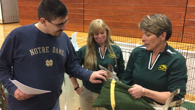 """Andrew Jordan, 29, of Poughkeepsie, left, pets """"Maddy,"""" a young red kangaroo, at an expo hosted by Abilities First at Dutchess Community College on Saturday. At right is Two by Two Zoo owner Heather Iannucci. At center is educator Sue Scalzo."""