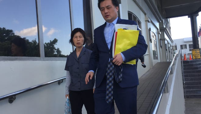 Yang Young Hwa, left, mother of Kwon Woo Sung, right, leave the District Court of Guam on Nov. 29 after Kwon was sentenced to almost three years in prison.