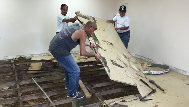Guam Department of Education facilities and maintenance personnel dismantle damaged classroom wooden floors, and replace them with new ones later on, at L.P. Untalan Middle School in Barrigada Friday morning.