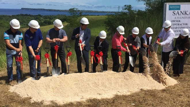 Jupiter Juno and Base Corp. officials shovel dirt to mark Thursday morning's groundbreaking for a $7.6 million, 33-unit residential subdivision in Agat. If everything goes according to plan, the project will be completed around June 2019.