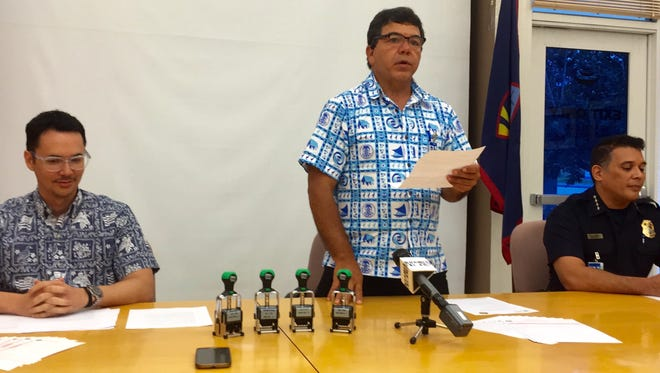 Guam Customs and Quarantine Agency Director James McDonald, center, talks about the smaller, much improved Guam customs declaration form during a news briefing Wednesday afternoon. Looking on are Guam Visitors Bureau President Nathan Denight, left, and Chief of Customs Vincent S.N. Perez, right. By Nov. 17, Customs will no longer accept the old forms.