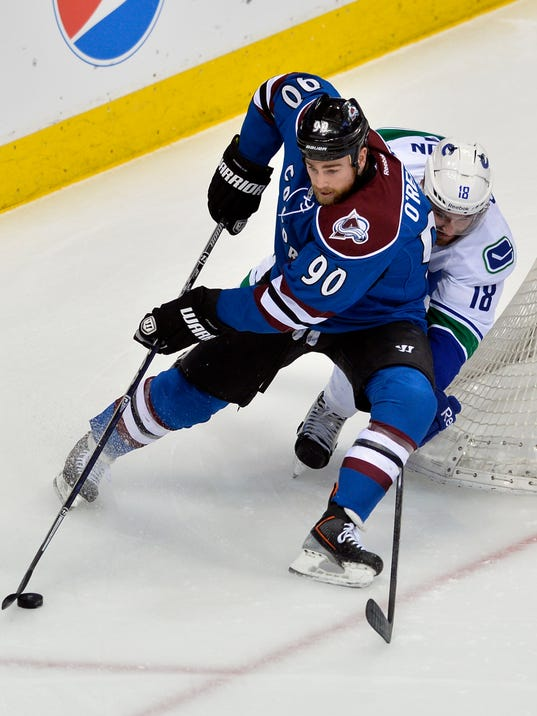 Colorado Avalanche center Ryan O'Reilly (90) moves the puck around Vancouver Canucks defenseman Ryan Stanton (18) during the first period of an NHL hockey game on Thursday, March 27, 2014, in Denver. (AP Photo/Jack Dempsey)