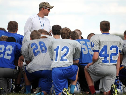 Reigning Northern 10 Conference Coach of the Year Gabe Helbert addresses his Wynford Royals during a preseason practice. Helbert says new rules to lessen the risk of concussions won't affect his program.