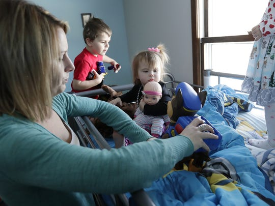 Kerri Matheys plays with her children, Brodan Allen, 4, and Taelynn Gardapee, 1, during a holiday party in their home on Thursday in Ashwaubenon. Matheys participated in an individualized parental support program through the Jessica Raymaker Memorial Support Fund for Family & Childcare Resources of Northeast Wisconsin.