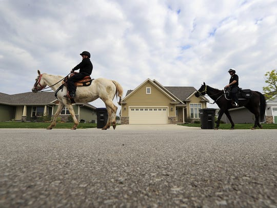 Green Bay Police Mounted Patrol officers Paul Vanhandel (left) and Sean Hamill ride horses through a neighborhood in Hobart during a training session.