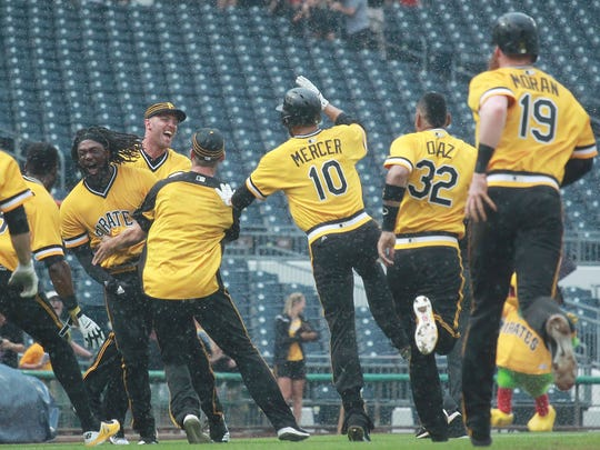 Pirates first baseman Josh Bell (left) celebrates with teammates after driving in the game-winning run against the Brewers.