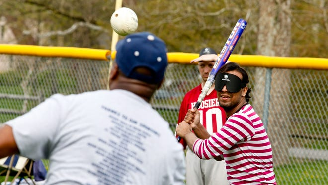 Eckron Ikramullah taking batting practice during the Indianapolis Thunder Beepball practice at Broad Ripple Park in Indianapolis, Saturday, April 18, 2015. Players wear masks to make all of their visual impairments equal. (Perry Reichanadter / for The Indianapolis Star)