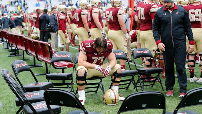 Boston College offensive lineman Jon Baker (77) sits alone on the bench during the final seconds of Syracuse's 28-20 win over Boston College at Alumni Stadium.