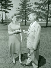 Mrs. Fred Kletzien presents the deed conveying title to the 15-acre Kletzien Indian Mound property from its owners to the Indian Mounds Holding Association. Ray Lightfoot accepts the document for the Association. The formal transfer finalized a sustained campaign by interested citizens to save the Indian mounds in the area.