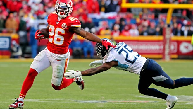 Jan 19, 2020; Kansas City, Missouri, USA; Kansas City Chiefs running back Damien Williams (26) runs the ball against Tennessee Titans cornerback Adoree' Jackson (25) during the third quarter in the AFC Championship Game at Arrowhead Stadium. Mandatory Credit: Jay Biggerstaff-USA TODAY Sports