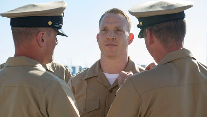 Chief Fire Controlman (Aegis) Daniel Billowitz (center), assigned to Aegis Ashore Missile Defense System (AAMDS) Romania, is pinned by his mentors during a chief petty officer pinning ceremony.