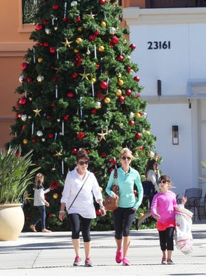 Valerie Bisco, left, Elizabeth Cameratta and Ella Cameratta, 8, shop at the Coconut Point mall on Monday morning.