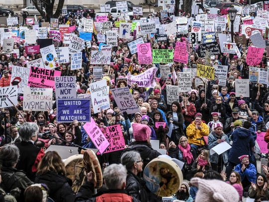 The Capitol grounds are awash with signs on Saturday, Jan. 21, 2017, as 8,000 to 9,000 people make their voices heard in the Women's March on Lansing.