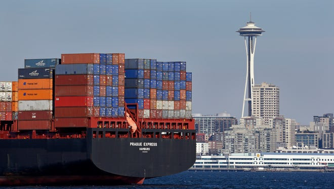 The Space Needle is seen just beyond a container ship anchored in Elliott Bay near downtown Feb. 15, 2015, in Seattle. A labor dispute between operators of the 29 West Coast port terminals and the International Longshore and Warehouse Union (ILWU), which has brought a worker slowdown, is stacking up ships and cargo containers from San Diego to Seattle,.