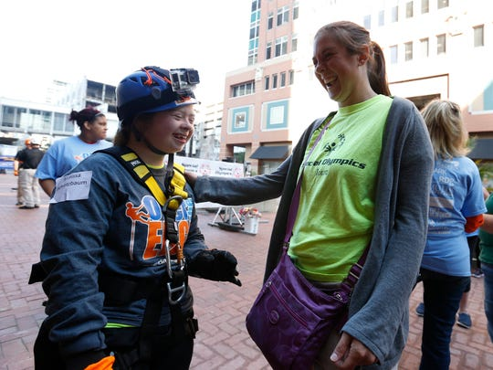 Special Olympics athlete Marissa Schletzbaum (left) laughs with sister Andrea Rindfleisch Wednesday, Sept. 16, 2015, after doing a tandem rappel down the side of The Financial Center during the Over the Edge fundraiser for Special Olympics Iowa.