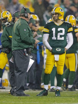 Green Bay Packers head coach Mike McCarthy talks with quarterback Aaron Rodgers (12) against the Dallas Cowboys at Lambeau Field.