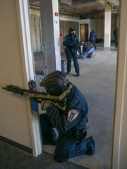 An OakTac officer watches to make sure the exit point is clear for the team to remove the victim.