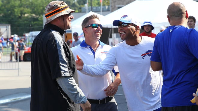 Brown head coach Mike Pettine (L) shares a laugh with Bills President Russ Brandon and GM Doug Whaley. Pettine was the Bills defensive coordinator two years ago.