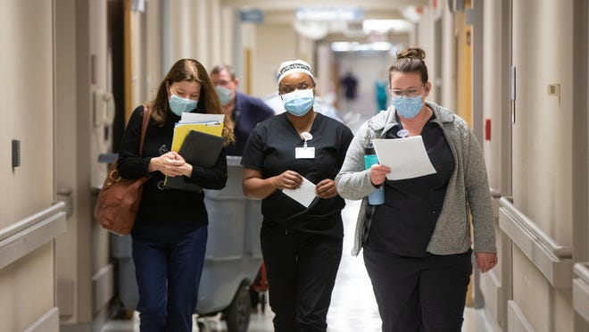 Salena Gillum, left, administrative director of medical surgical and critical care at Stormont Vail Hospital, walks down a hallway with nurses on Nov. 18 as COVID-19 cases put the hospital at capacity.