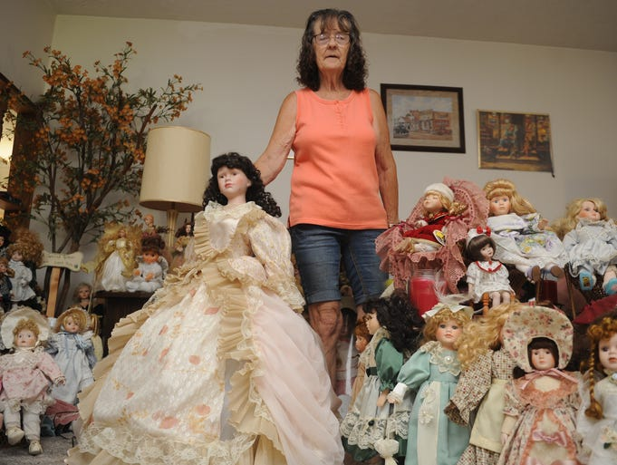 Donna Felton stands in her Tyndall living room with her doll collection. Felton has been collecting dolls for four years. She has an estimated 750.