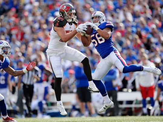 Buffalo Bills outside linebacker Matt Milano (58) intercepts a pass to Tampa Bay Buccaneers' Cameron Brate (84) during the first half of an NFL football game as Jordan Poyer (21) watches, Sunday, Oct. 22, 2017, in Orchard Park, N.Y. (AP Photo/Adrian Kraus)