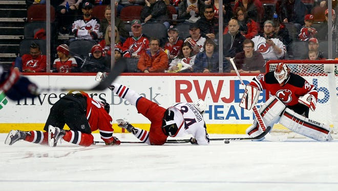 New Jersey Devils defenseman Dalton Prout, left, is called for a penalty on Columbus Blue Jackets right wing Josh Anderson (34) in front of Devils goalie Cory Schneider (35) during the second period of an NHL hockey game, Sunday, March 19, 2017, in Newark, N.J. (AP Photo/Adam Hunger)