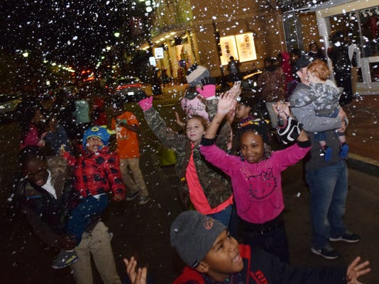 """Children play in the """"snow"""" made by snow machines located in downtown Alexandria Thursday evening. The snow was part of Alexandria's newest festival, Alex Winter Fete."""