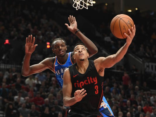 Portland Trail Blazers guard CJ McCollum drives to the basket on Oklahoma City Thunder forward Jerami Grant during the second half of an NBA basketball game in Portland, Ore., Saturday, March 3, 2018. The Blazers won 108-100. (AP Photo/Steve Dykes)