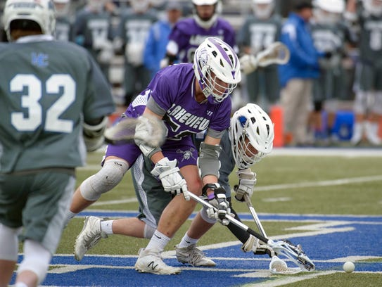 Lakeview's Jerry Haadsma (52) battles with Harper Creek's