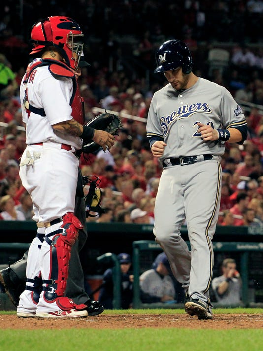 Milwaukee Brewers' Jonathan Lucroy, right, scores past St. Louis Cardinals catcher Yadier Molina, left, on a single by Aramis Ramirez during the fourth inning of a baseball game Thursday, Sept. 18, 2014, in St. Louis. (AP Photo/Jeff Roberson)