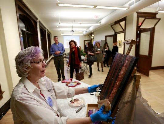 Artist Val Berkely, of Wausau, demonstrates on an oil