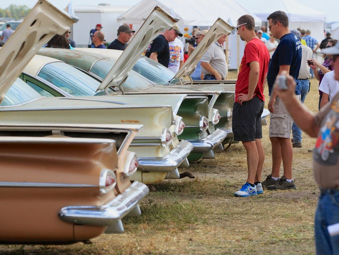 Potential bidders look over vintage 1959 Chevrolets lined up in a field near the former Lambrecht Chevrolet car dealership in Pierce, Neb. An estimated 25,000 bidders from around the U.S. and the world converged on the small town of 1,700 for a two-day auction Saturday and Sunday that featured 500 old cars and trucks, mostly Chevrolets, that went unsold during the dealership's five decades in business. People also could bid online.