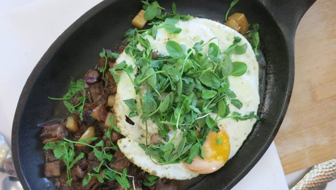 The braised beef short rib hash skillet on the brunch menu at the Stand in Birmingham is topped with two eggs and includes diced fingerling potatoes and onions, spring pea shoots and fresh thyme.