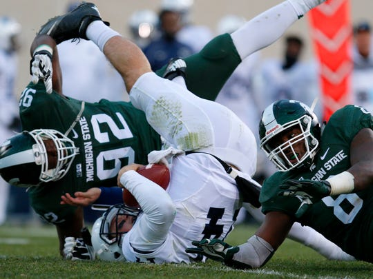 Penn State quarterback Christian Hackenberg, center, is sacked by Michigan State's Joel Heath (92) and Lawrence Thomas during the second quarter of Saturday's game in East Lansing, Mich. Michigan State earned a 55-16 victory to claim the Big Ten East title and advance to the Big Ten championship game against Iowa.