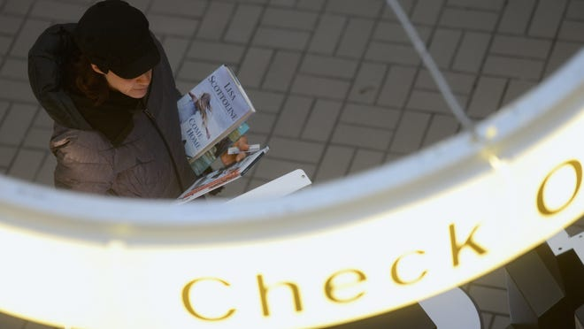 A woman checks out her book selections at the downtown branch of the Brown County Library in Green Bay on Thursday.