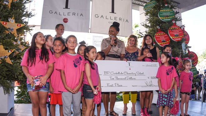 Renee Chisolm, center, T Galleria Guam general manager, congratulates students, parents, employees and family members of B.P. Carbullido Elementary School for winning first place in their division in the T Galleria by DFS, Guam's Fifth Annual DFS Festival of Trees competition in Tumon on Saturday, Jan. 6, 2018. As part of the holiday celebration, the Galleria invited participants from the island's elementary schools and high schools to demonstrate their creative skills in decorating Christmas trees with student-designed ornaments. This year, 10 elementary schools and all six public high schools took part in the competition.