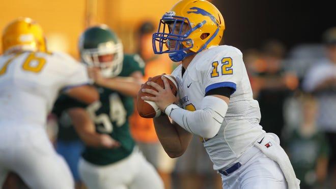 Carmel High School's Michael Viktrup (12) looks to pass the football against Trinity High School during the first half of play at Trinity High School in Louisville, Kentucky.       August 29, 2014