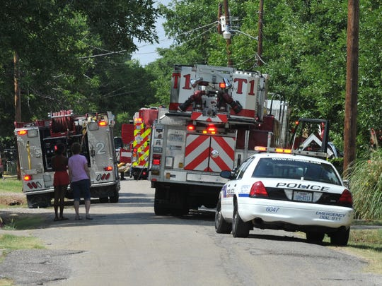 Fire engines and police cars blocked the roadway while Wichita Falls firefighters work to control a structure fire on Landon Lane Sunday afternoon.