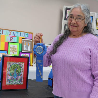 Doris Dowdy holds her first place ribbon for her peacock at the Ouachita Council on Aging Relaxation Art Show sponsored by Kilpatrick Funeral Home.