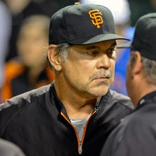 San Francisco Giants manager Bruce Bochy (15) talks with umpire Hunter Wendelstedt (21) during a rain delay in the Chicago Cubs game against the San Francisco Giants at Wrigley Field. The game was called shortly after this.
