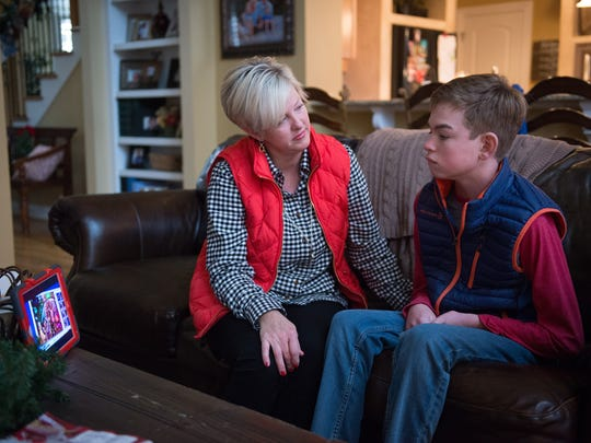Julie Koch sits with her son Alex Koch at their home