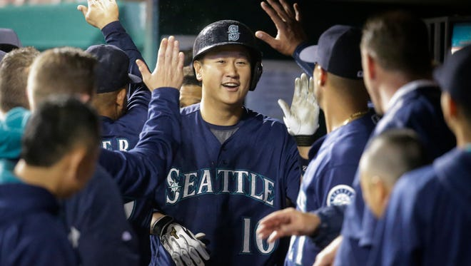 Seattle Mariners' Dae-Ho Lee (10) celebrates in the dugout after hitting a solo home run off Cincinnati Reds relief pitcher Jumbo Diaz during the ninth inning of a baseball game, Friday, May 20, 2016, in Cincinnati. (AP Photo/John Minchillo)