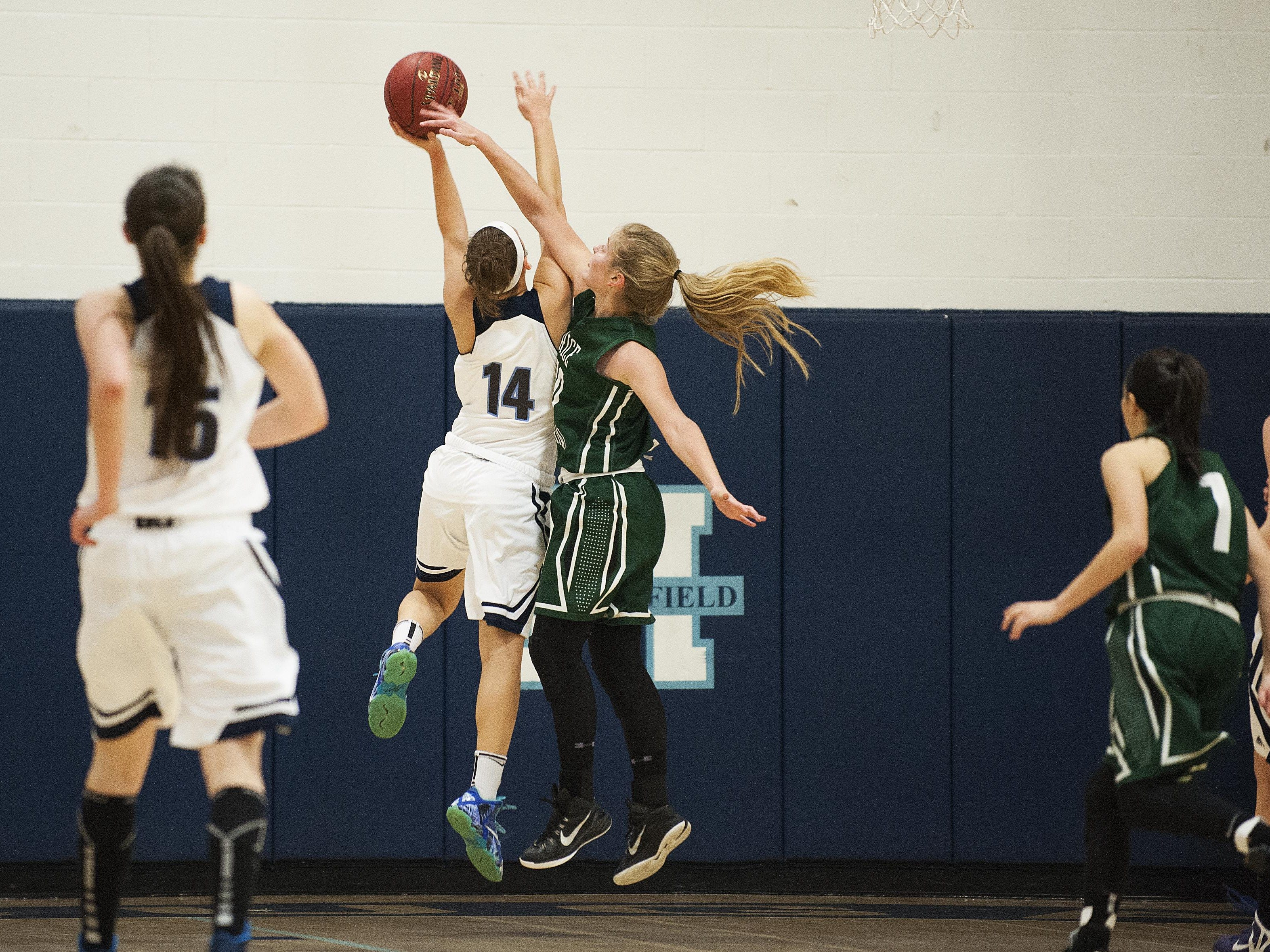 Rice forward Stephanie Langlais (10) tries to block the shot by Mount Mansfield forward Katie Estes (14) during the girls basketball game between the Rice Green knights and the Mount Mansfield Cougars at MMU High School on Friday night December 4, 2015 in Jericho.