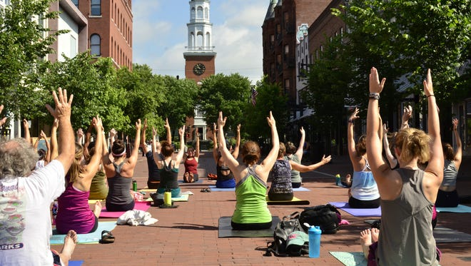 About 20 people took part in a yoga class on Church Street in Burlington on Sunday, June 18, 2017. The class is part of a summer-long series where each week, donations are given to a different local nonprofit.
