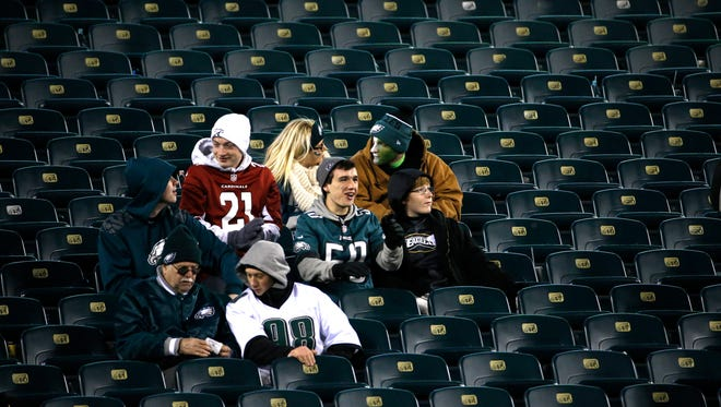 Fans sit in a nearly-empty section of Lincoln Financial Field during the second half of an NFL football game between the Philadelphia Eagles and the Arizona Cardinals, Sunday, Dec. 20, 2015, in Philadelphia.