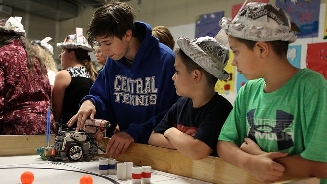 Volunteer Carson Green (left) shows brothers Adan (center) and Alejandro Reyes how a robot works at the the grand opening of STEAM Central at Stephens Central Library on Thursday, March 23.
