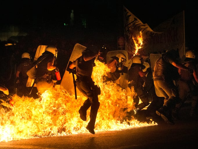 Riot police officers run through fire as anti-austerity