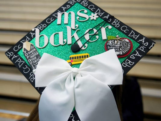 A graduate wears a customized cap at York College's winter commencement in December. With customized mortarboards increasingly popular, an Indiana University student, Marc Goldberg, has created a business called TasselToppers.com. Goldberg has now shipped several hundred thousand customized mortarboard designs, which let buyers choose background colors and add images and text. T
