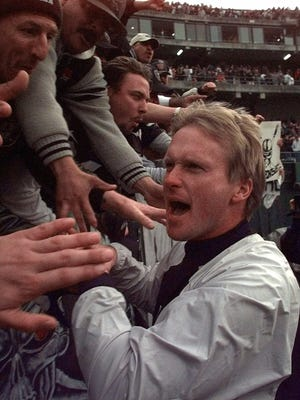 Oakland Raiders'  coach Jon Gruden celebrates with fans after the Raiders'  30-21 victory over the Seattle Seahawks Sunday, Dec. 5, 1999,  in Oakland, Calif.