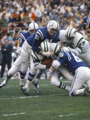 Baltimore Colts linebacker Don Shinnick (66) closes on a tackle of the New York Jets' Matt Snell with Ordell Brasse (81) during Super Bowl III.